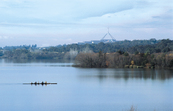 Rowers, early morning on Lake Burleigh Griffin, Canberra. ACT. Profile of Parliament House buildings in background. Taken late autumn.