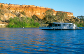 A Murray River Houseboat passing ancient cliffs at sunset, j... [ID:6439]
