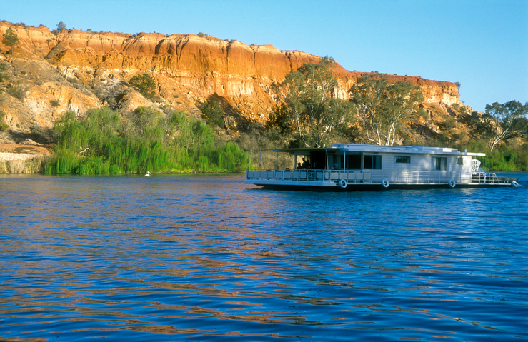 A Murray River Houseboat passing ancient cliffs at sunset, j...