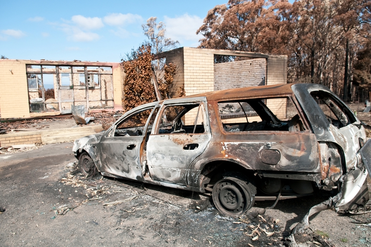 A burnt-out car and house at Kinglake after the 'Black Satur...