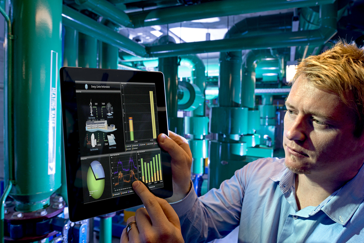 A man looking at a tablet in an energy facility