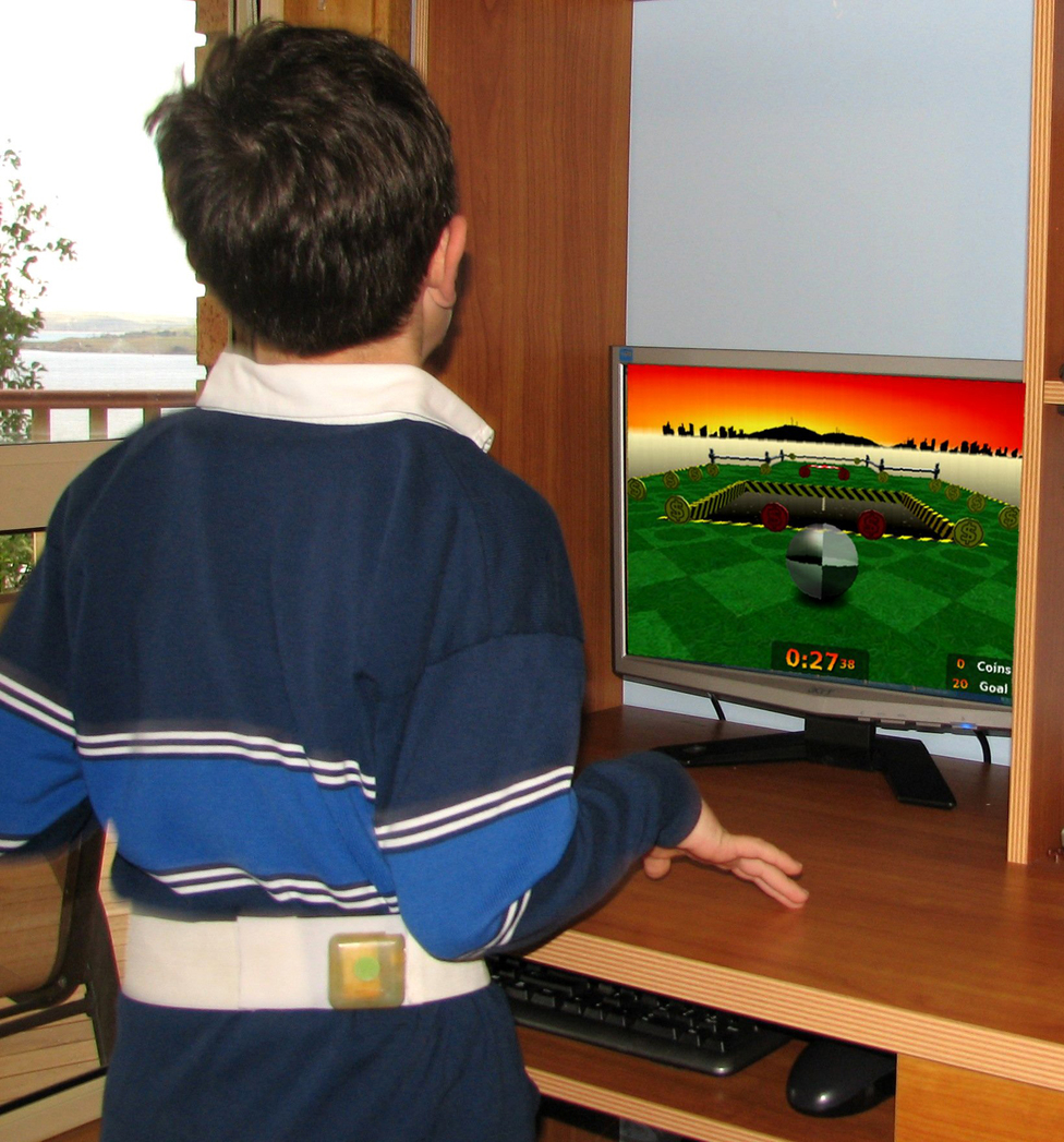 A child fitted with an accelerometer trials a computer game ...