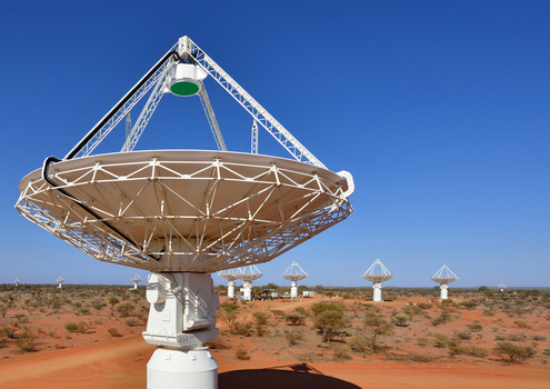 Close up of a radio astronomy telescope with several more in the backgro...