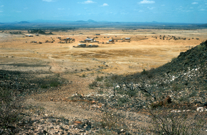 A rough bush track leads down to a small village on the edge of vast plains in Kenya, Africa. 1981.