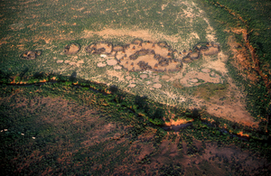 A dry watercourse borders a village on the Manyatta El Bata Plains in Kenya, Africa. 1981.