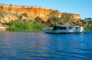 A Murray River Houseboat passing ancient cliffs at sunset, just upstream from Renmark, SA. 2002.