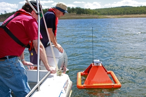CSIRO scientists inspect one of the floating nodes monitoring Lake Wivenhoe
