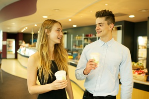A man and woman chatting outside a cafe