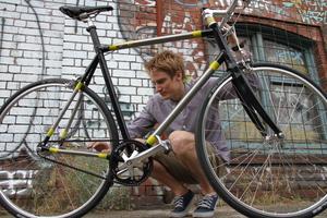 Man squats behind bicycle