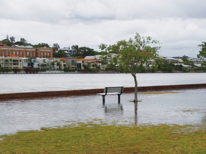 A bench at a park submerged from rising water levels