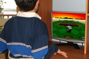 A child fitted with an accelerometer trials a computer game designed to encourage movement.