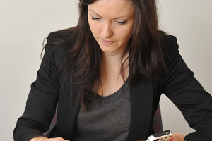 A woman seated at a desk using mobile devices